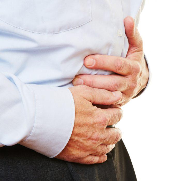 Älterer Mann mit Bauchschmerzen hält seinen Bauch mit den Händen fest